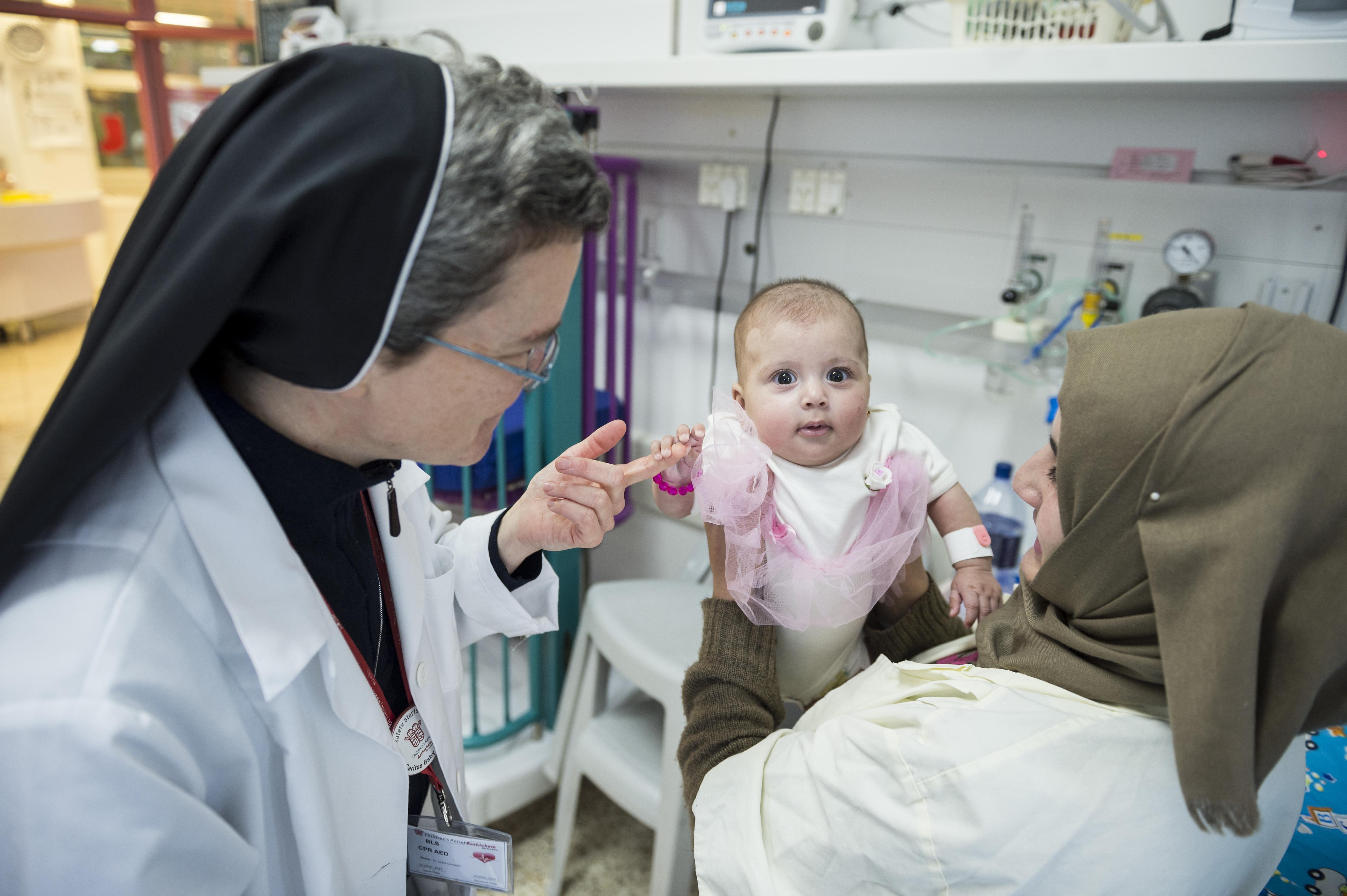 una bambina di pochi mesi sorride assieme alla mamma e a una suora