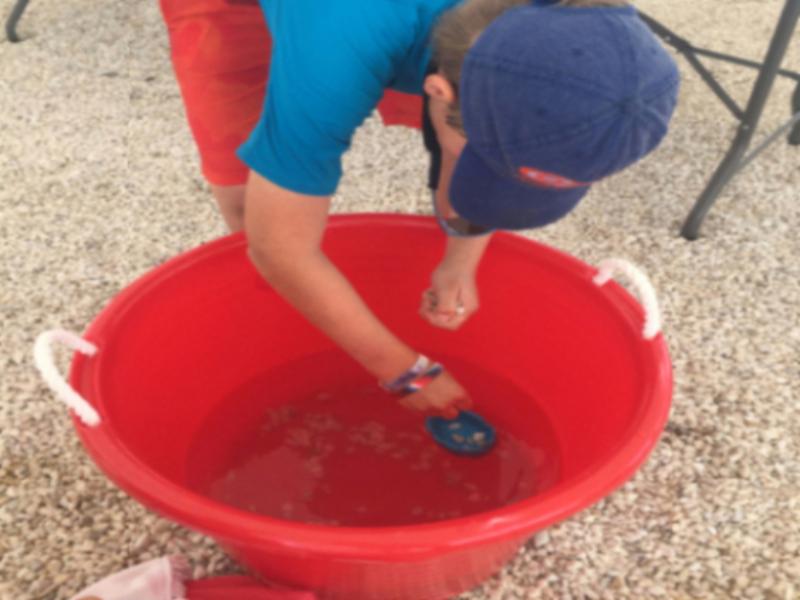 Brendan camper tests his clay pot's buoancy using US Sailing's STEM program!