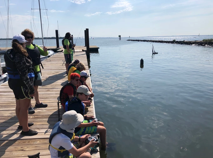Brendan Sailing campers participate in in remote control sail-boating off the dock at Annapolis Sailing School