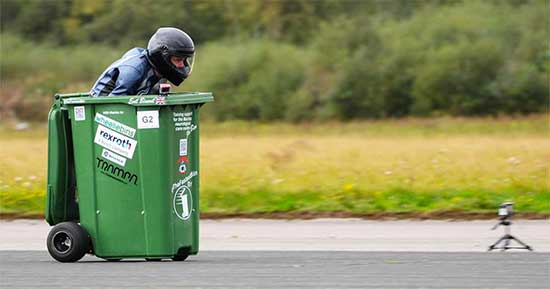 Man wearing helmet hunched down in green trash can.