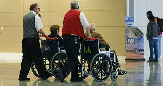 Two male wheelchair staff pushing wheelchairs in airport.