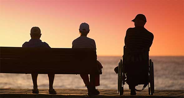 Two older people sitting on a bench watching the sunset along with one wheelchair user.