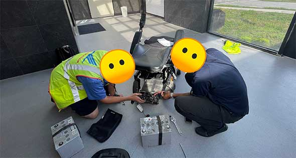 Two airline employees removing two large batteries from wheelchair.