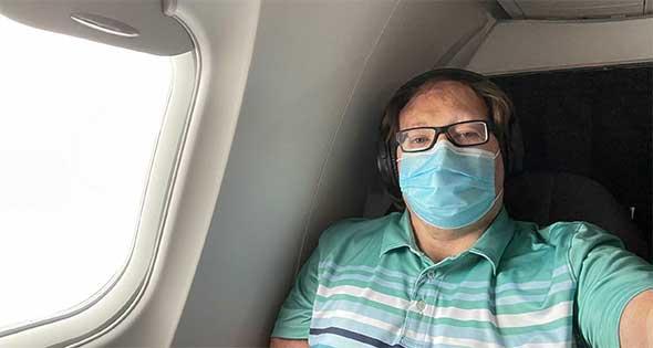 John takes selfie during flight while wearing face mask.