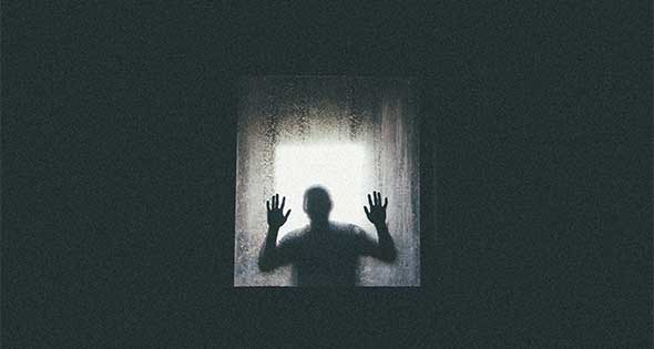 Man isolated, with his hands pressed against a window.