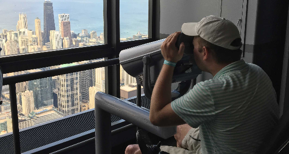 Wheelchair user looking at city skyline through accessible viewfinder.