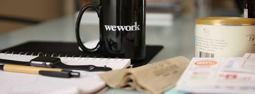 """Ein Arbeitsplatz: Tasse mit Aufschrift """"wework"""" , aufgeschlagenes Notizbuch, Stift und Smartwatch; Bild: Charles Koh, Unsplash"""