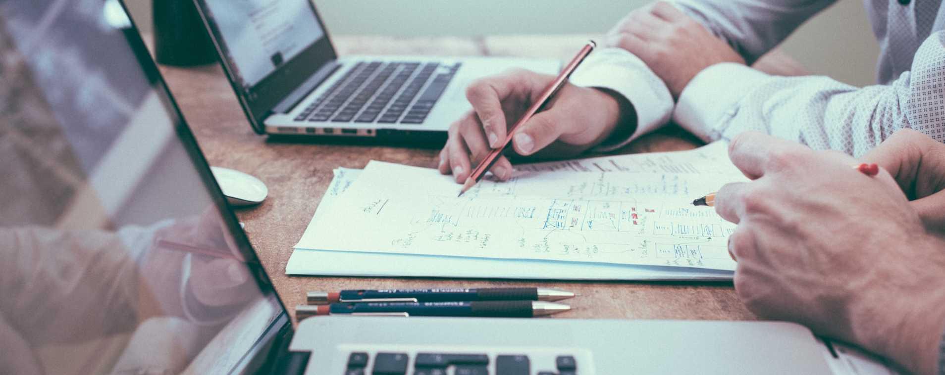 zwei aufgeklappte Laptops, dazwischen handschriftliche Notizen, die von zwei Personen bearbeitet werden